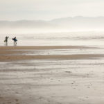 surfers_in_wetsuits_with_surfboards_walk_along_wide_beach_with_tide_out_towards_hazy_water